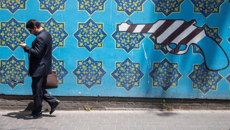 Ein Mann in Teheran vor einer Anti-USA-Grafik