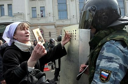 A woman holds an icon as she speakes with a Russian riot policeman during a rally of The Other Russia movement in St.Petersburg on April 15.