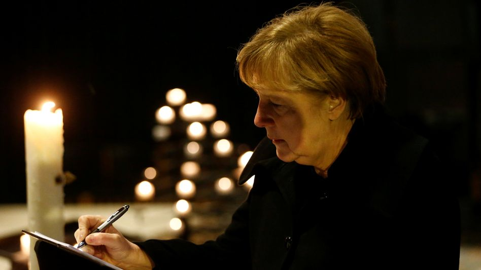 German Chancellor Angela Merkel signs the book of condolence for the victims of the Monday night attack.
