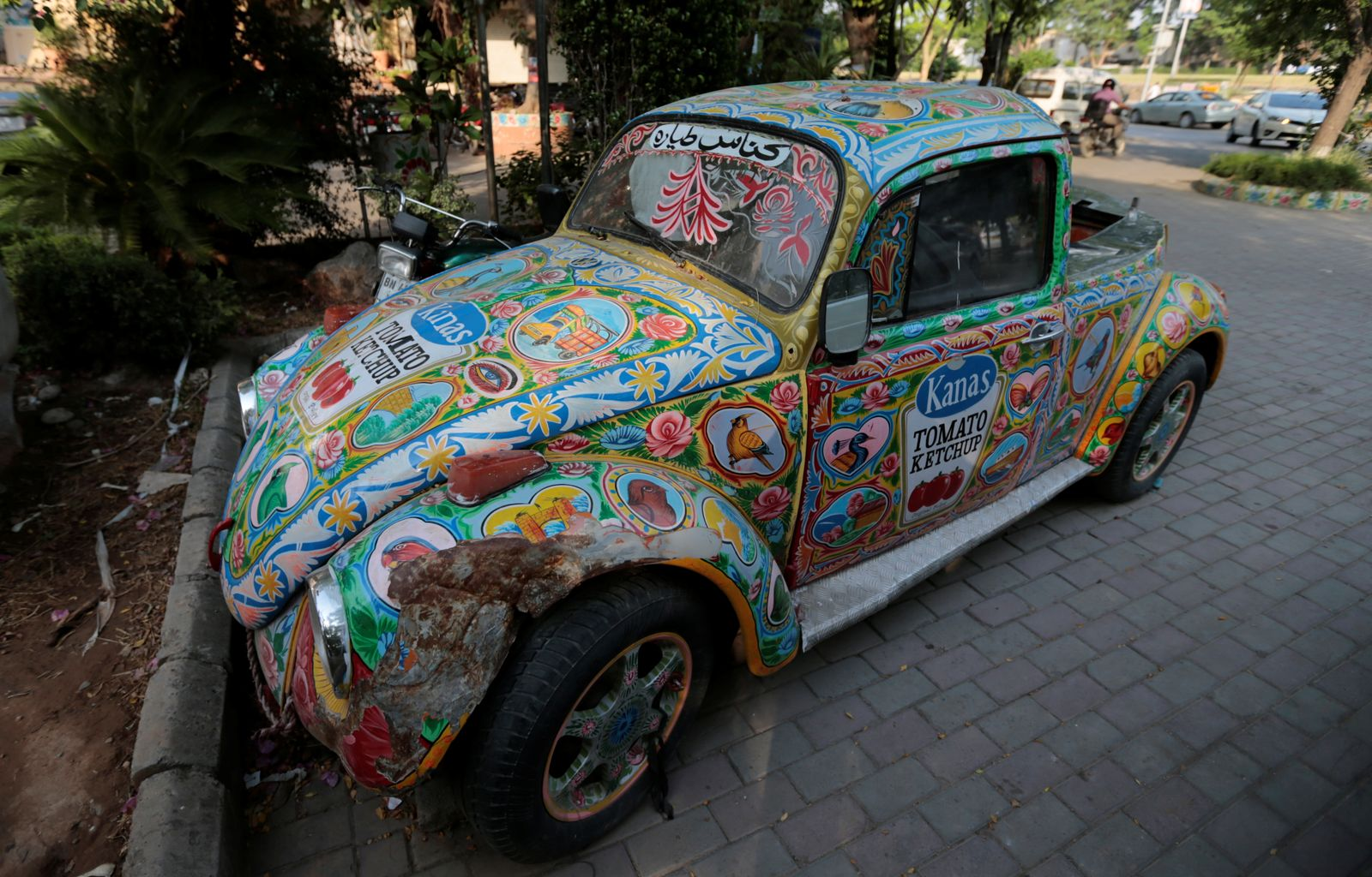 An old VW Beetle painted with truck art is seen abandoned in a parking lot in Islamabad