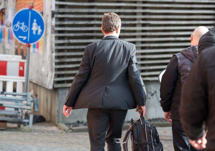 """dpatopbilder - 23.10.2019, Hamburg: AfD-Mitbegründer Bernd Lucke (l) verlässt nach einer Vorlesung an der Universität Hamburg das Gelände. Die Vorlesung Luckes ist erneut gestört worden. (zu dpa """"Erneut Vorlesung von AfD-Mitbegründer Lucke gestört"""") Foto: Daniel Bockwoldt/dpa +++ dpa-Bildfunk +++   Verwendung weltweit"""