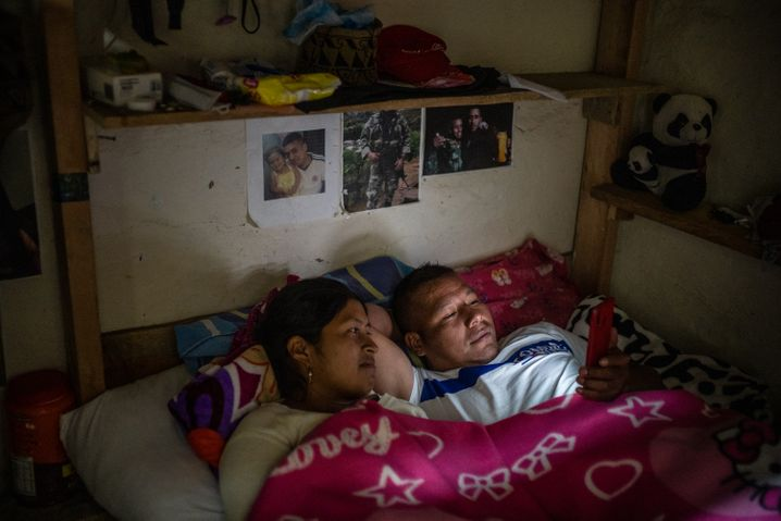 Libia Stella Nene and her boyfriend, Luis Eduardo Caso, in their bedroom, in front of wall photos of their time as FARC fighters in the jungle.