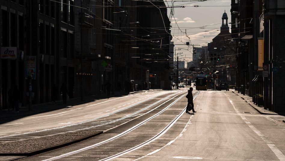 A pedestrian crosses an empty street in Berlin.