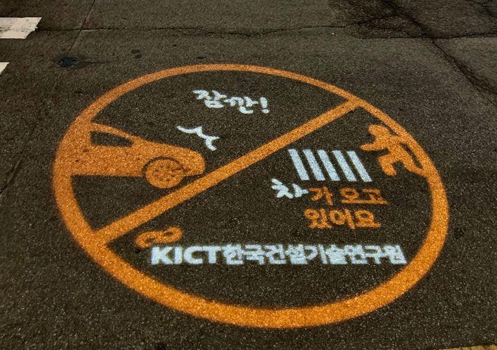 """""""Stopp! Ein Auto nähert sich!"""" Das System projiziert Warnhinweise wie diesen auf die Straße."""