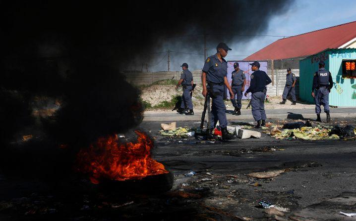 Polizisten vor brennenden Barrikaden in Khayelitsha