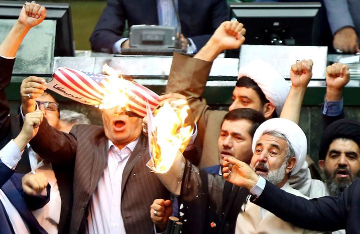 Members of the Iranian parliament burn an image of the U.S. flag on paper in protest against President Donald Trump's decision to withdraw from the nuclear deal with Iran.