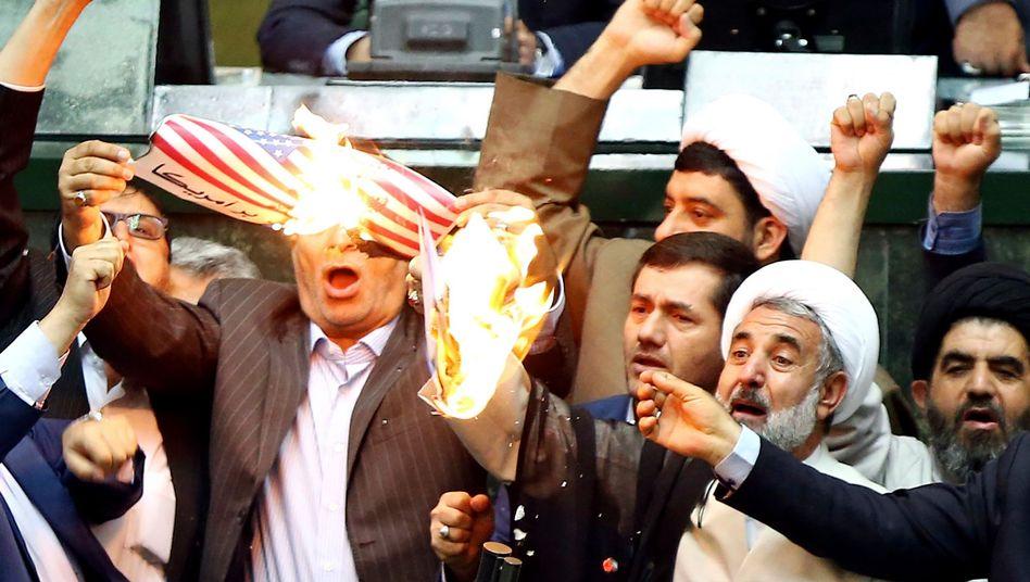 Iranische Abgeordnete verbrennen eine US-Flagge aus Papier