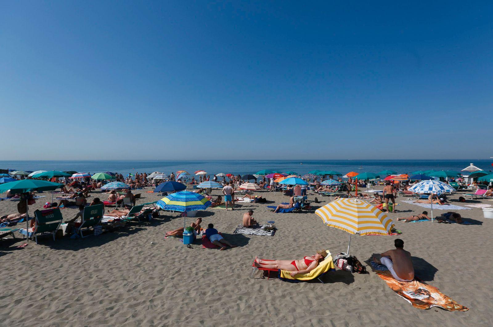 People sunbath at Ostia beach, west of Rome