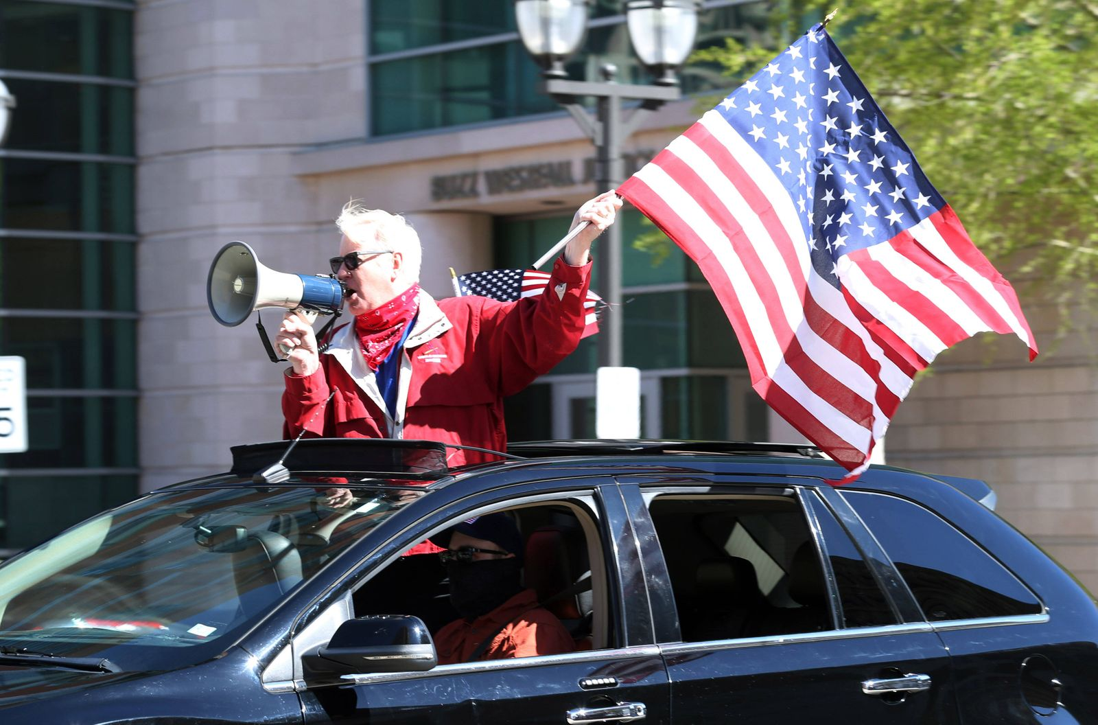 People wave American flags as they sound their horns, driving by the St. Louis County Government Center, during a drive
