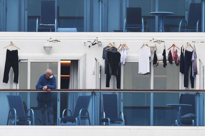 """Passagier mit Mundschutz auf der """"Diamond Princess"""" vor der japanischen Hafenstadt Yokohama"""