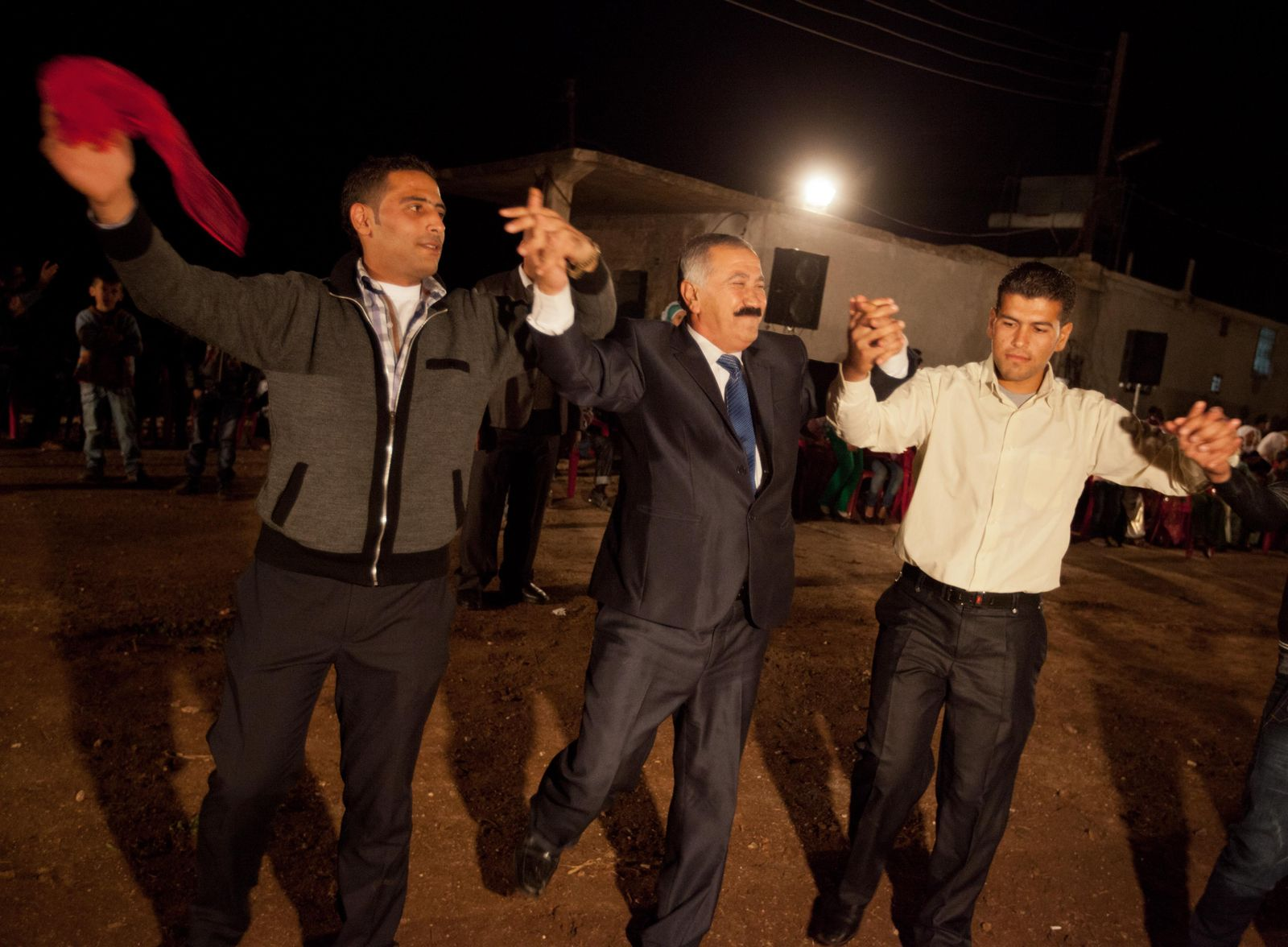 Men dance and play instruments during a Kurdish Sunni