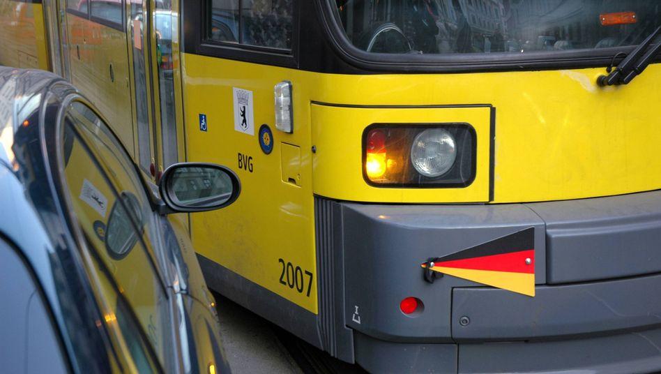Straßenbahn fährt knapp an einem geparkten Auto vorbei