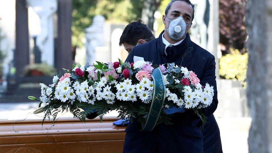Bestatter und Friedhofswärter bei der Grablegung einer an Covid-19 verstorbenen Person im norditalienischen Bergamo