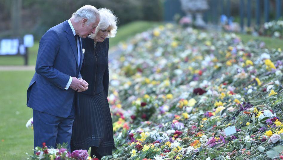 Thronfolger Charles mit Ehefrau Camilla vor einem Blumenmeer in London: Tiefe Trauer
