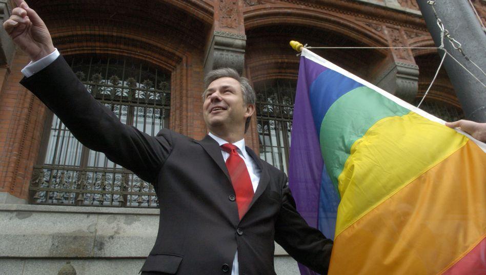 Berlins Regierender Bürgermeister Klaus Wowereit 2004 mit Regenbogenfahne vor dem Berliner Rathaus