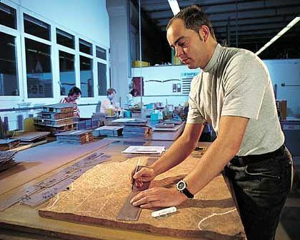 Schreiner bei Furnierauswahl: Für jedes Teil der Holzinnenausstattung werden geeignete Hölzer ausgewählt und zugeschnitten