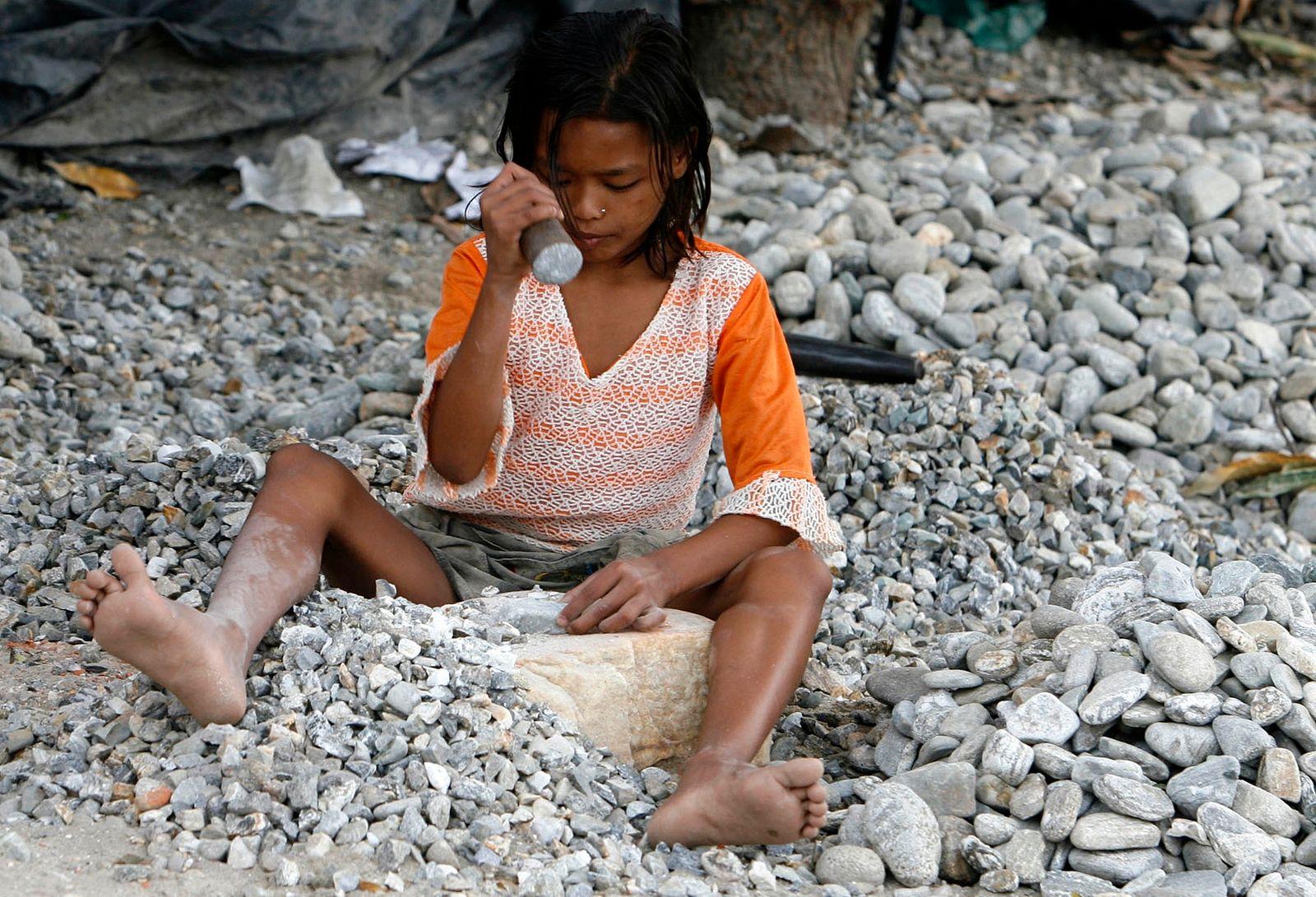Nine-year old Ganga Burman, a child labourer, breaks stones in Siliguri