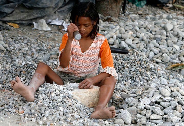 Ein Mädchen schlägt in Indien Steine klein, wie sie auch nach Deutschland verkauft werden (Archivbild)
