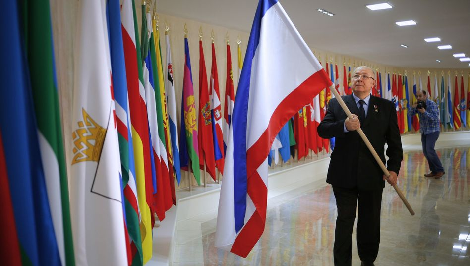 Russian lawmaker Alexander Chekalin adds the Crimea flag to the collection of regional flags in the Russian Federation Council building.