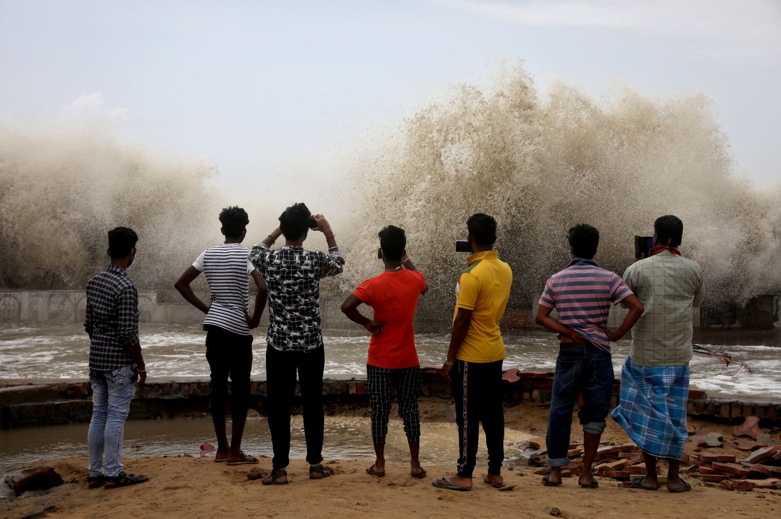 People take pictures of waves breaking on a beach front following Cyclone Yaas in Digha