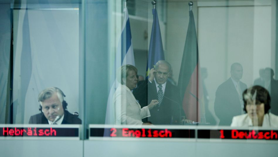 German Chancellor Angela Merkel and Israeli Prime Minister Benjamin Netanyahu seen in the reflection of the interpreter's booth at a Berlin press briefing in 2009.