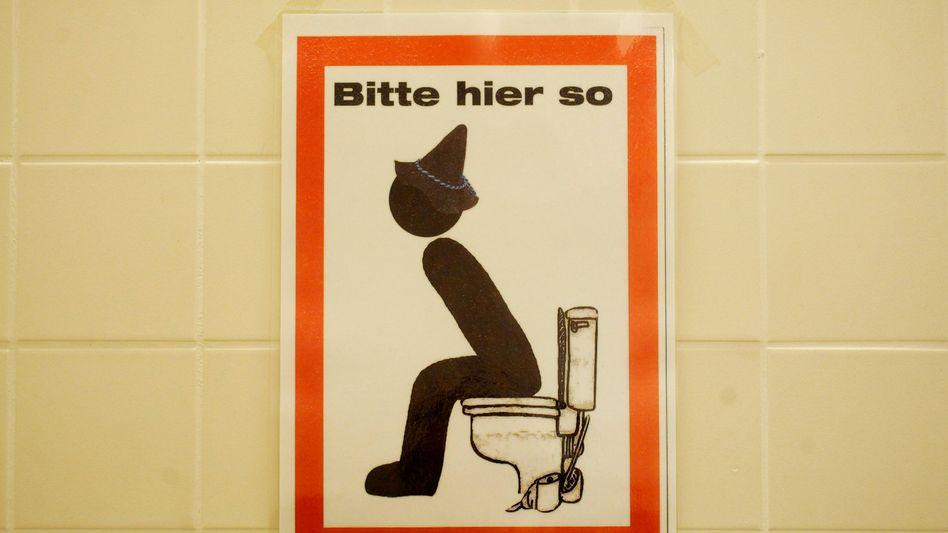 Toilettenschild: Ob Stehendpinkeln eine Pflichtverletzung ist, ließ das Gericht offen