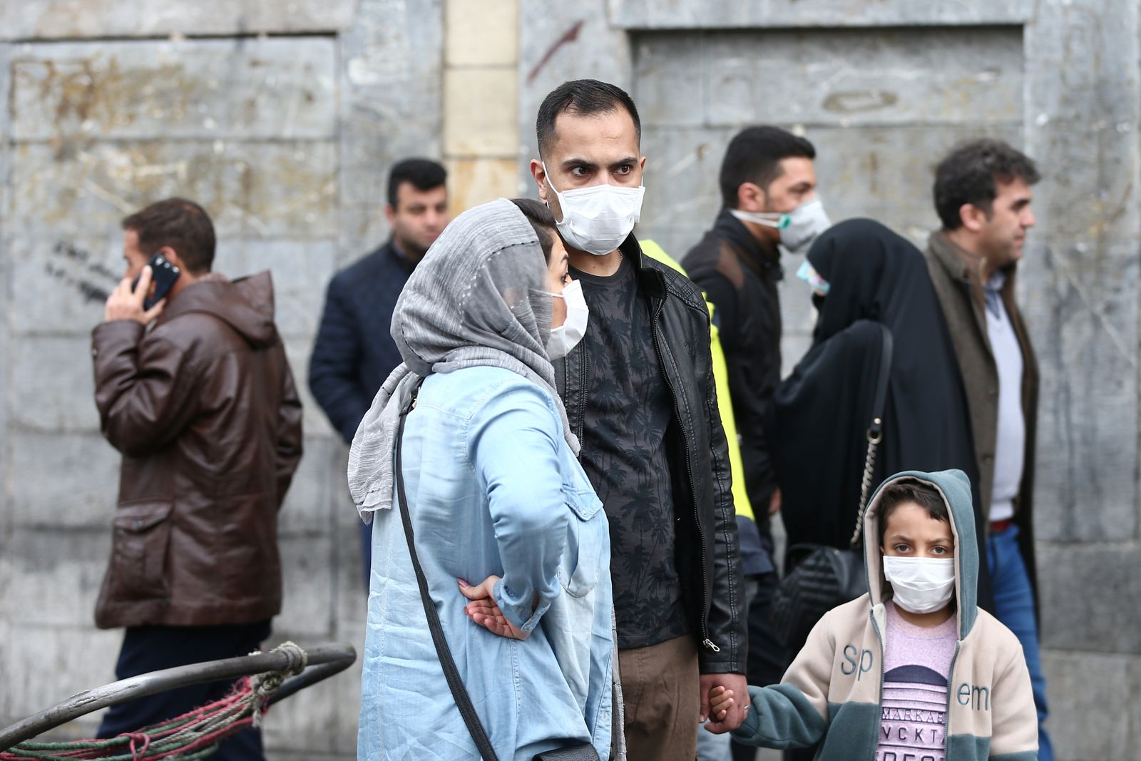 Iranian family wear protective masks to prevent contracting a coronavirus, as they stand at Grand Bazaar in Tehran
