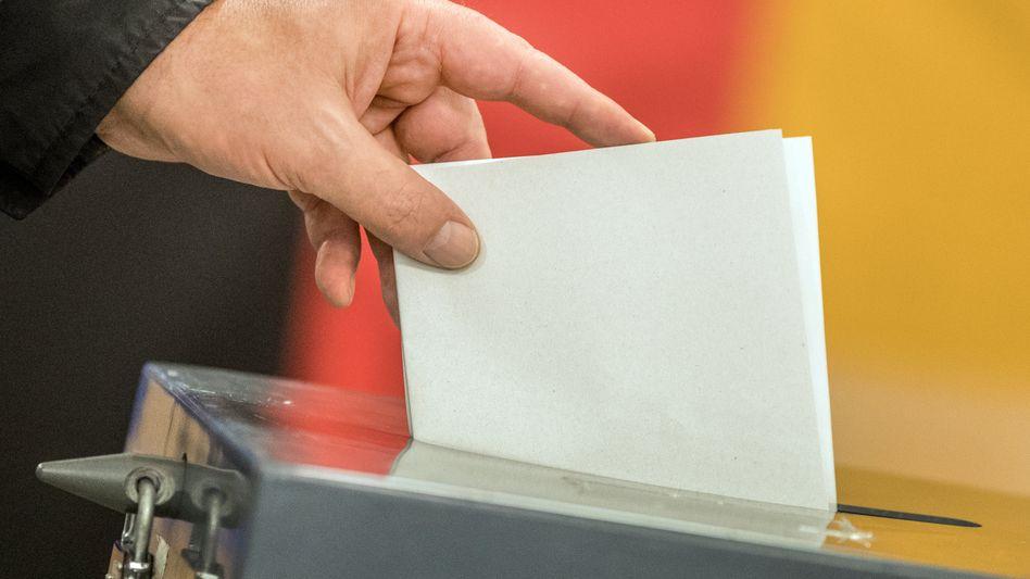 Einwurf eines Stimmzettels in eine Wahlurne
