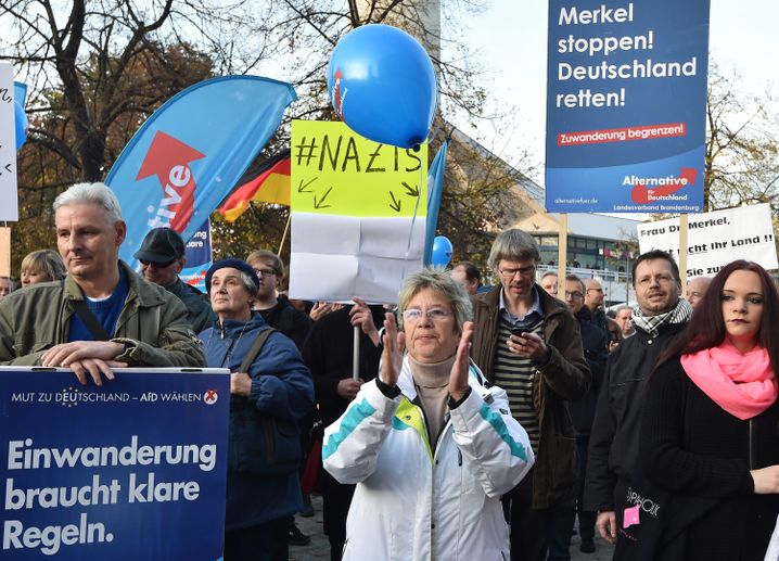 """Protesters with the Alternative for Germany Party at a demonstration in Berlin on Saturday hold up signs with slogans like, """"Clear rules are needed for immigration,"""" """"Limit immigration"""" or """"Mrs. Merkel, this isn't your country! Resign!"""""""