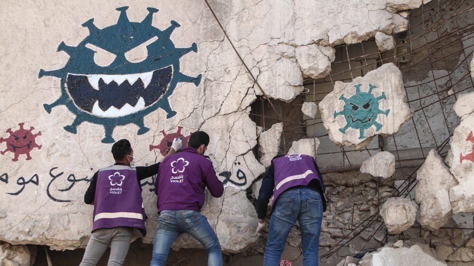 Corona-Warnung an zerstörtem Gebäude im nordsyrischen Idlib: Der Staat lässt die Syrer ziemlich allein