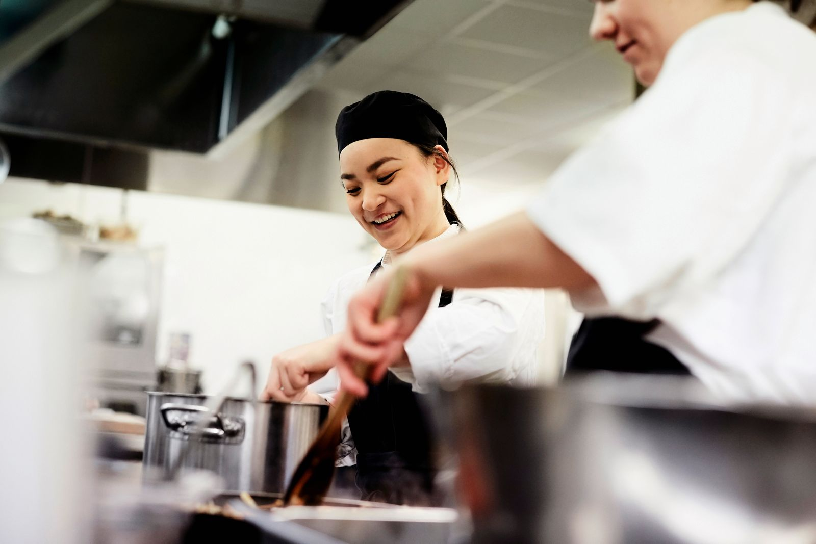 Smiling female chef student with colleague cooking food in commercial kitchen