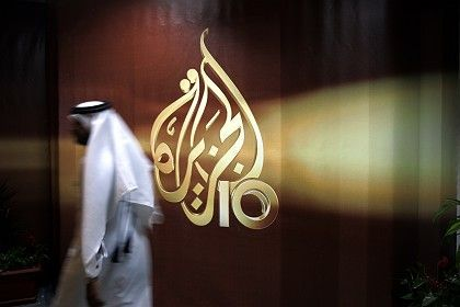 An employee of the news channel Al Jazeera passes by the station's logo in Doha, Qatar. Press freedom is a big issue in many Islamic countries.
