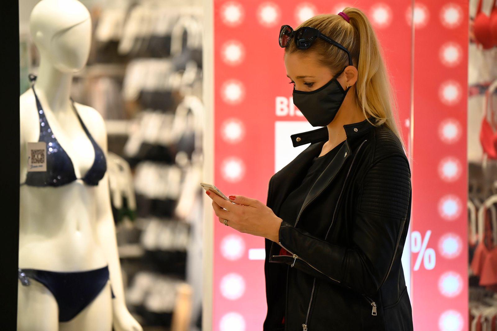 Frau trägt Mundschutzmaske beim Shopping, SALE, Preisnachlässe, am Smartphone, Corona-Krise, Stuttgart, Baden-Württembe