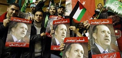 Palestinian Hamas supporters hold pictures of Turkish Prime Minister Recep Tayyip Erdogan during a rally in Beirut.