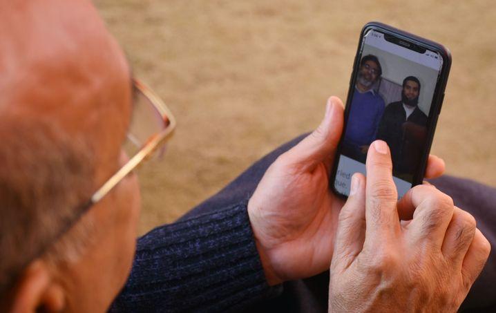 Ein Verwandter schaut sich ein Bild von Naeem Rashid und dessen Sohn Talha an. Beide wurden bei dem Terroranschlag ermordet