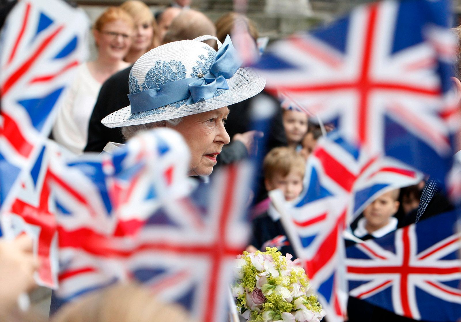 Britain's Queen Elizabeth is surrounded by flags waved by children while leaving after a service marking the tercentenary of St Paul's Cathedral in London