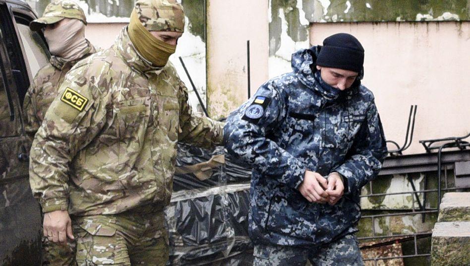 Ein Offizier des russischen Nachrichtendienstes FSB (l.) und ein ukrainischer Marinesoldat