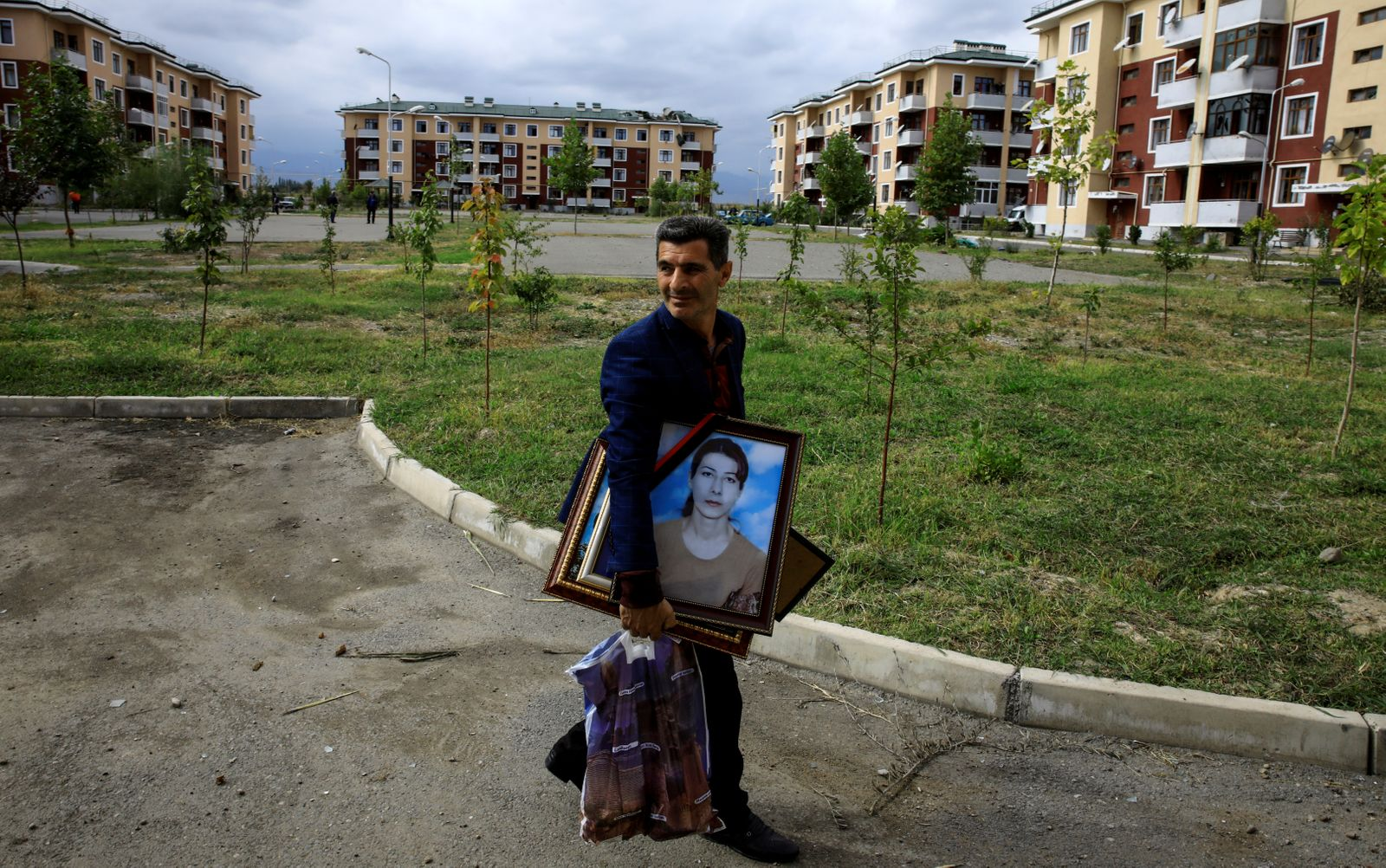 Iman Abisiv carries his belongings from his damaged home after a ceasefire begins during the fighting over the breakaway region of Nagorno-Karabakh in the city of Terter