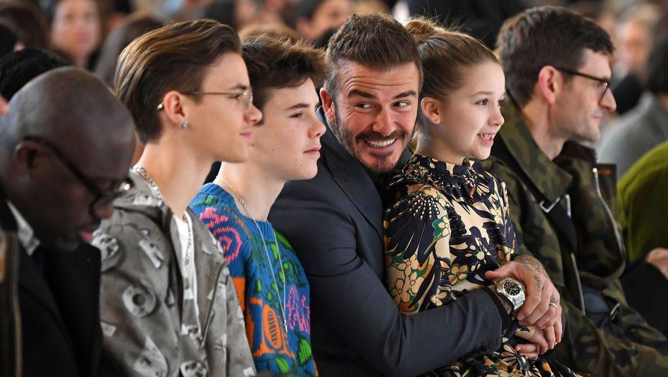 Romeo, Cruz und Harper Beckham verfolgen mit Vater David Beckham eine Modenschau von Mutter Victoria