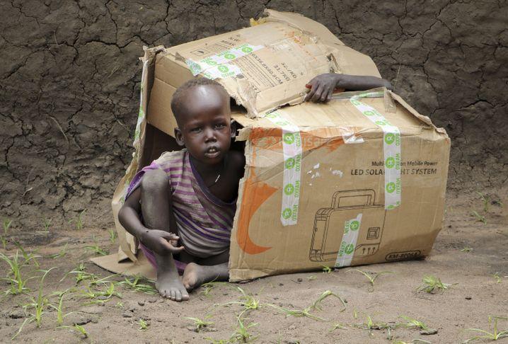 Zwei Jungen im Südsudan spielen in einem Pappkarton (Symbolbild)
