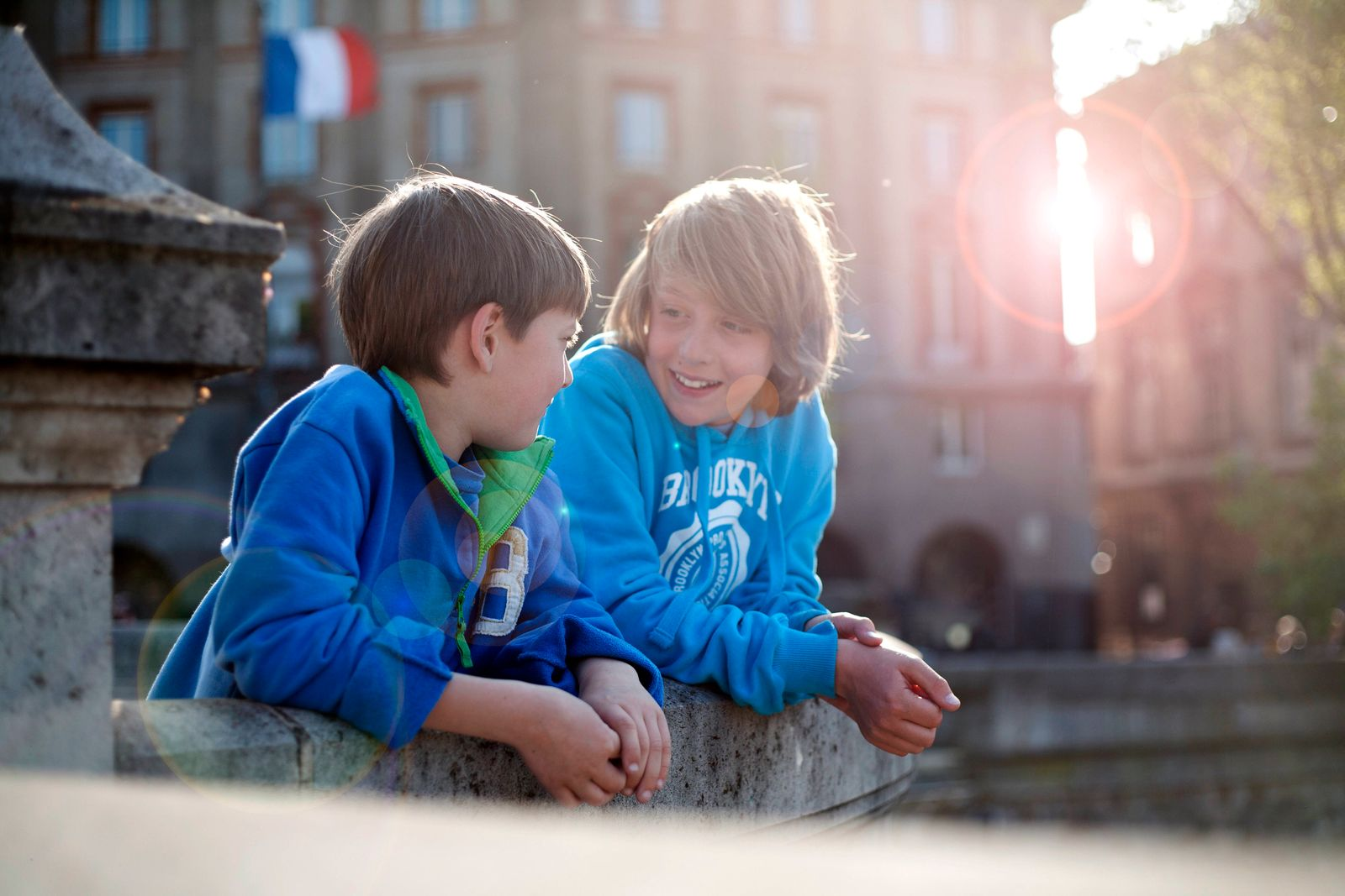 Boys talking while leaning on retaining wall in city model released Symbolfoto AJOF01543