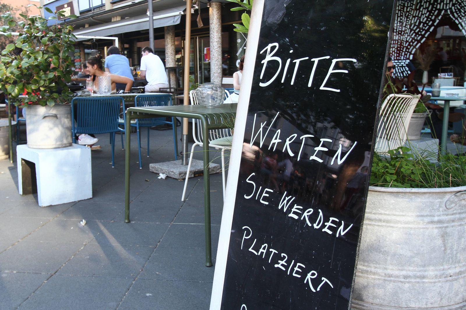 Schild mit Aufschrift bitte warten, Sie werden platziert, steht vor einem geöffneten, aber weitgehend leeren Restaurant