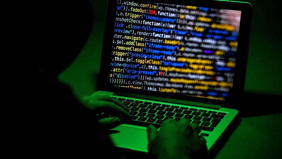 Ein Mann sitzt bei grünem Licht vor einem Computer, auf dem perspektivisch verzerrte Codezeilen zu sehen sind