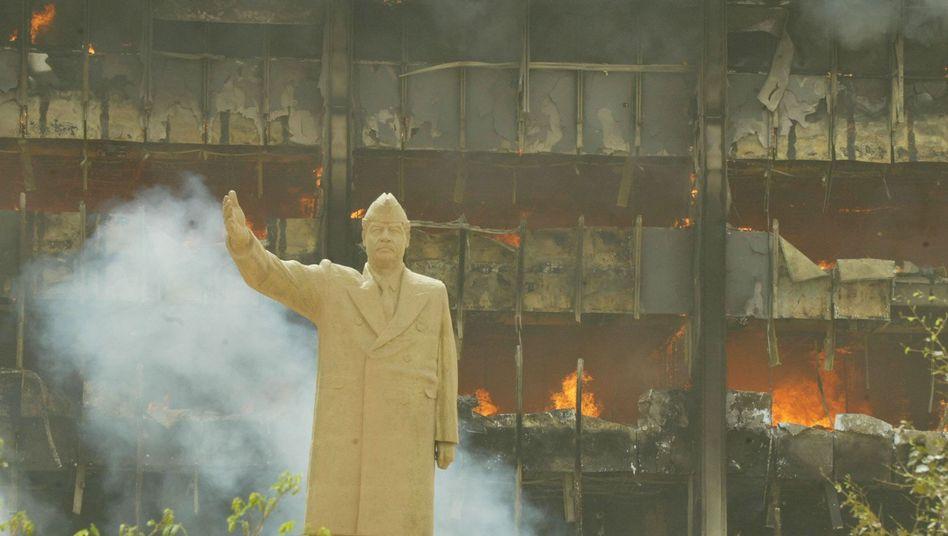 Noch stand sie: Die Statue des ehemaligen irakischen Staatspräsidenten Saddam Hussein im April 2003 vor dem brennenden Öl-Ministerium in Bagdad