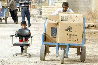Monitore sind auch im Irak begehrt: Ein Mann und sein Sohn bei Plünderungen von Regierungseinrichtungen in Südost-Bagdad