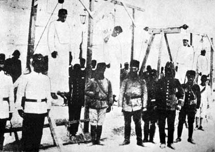 Völkermord: Türkische Soldaten neben erhängten Armeniern in Alep (um 1915)