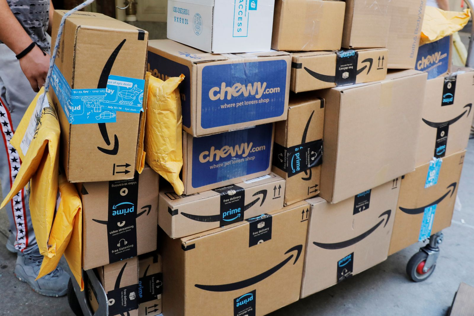 A delivery cart loaded with a number of packages from Amazon stands on a sidewalk in New York City