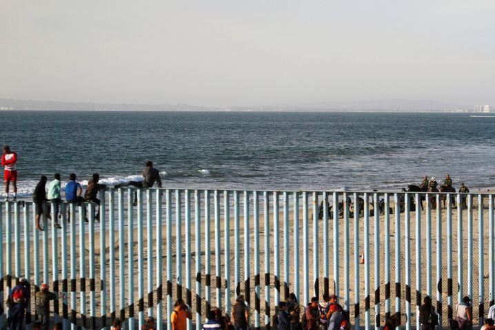 Migranten sitzen auf dem Grenzzaun zwischen Mexiko und den USA