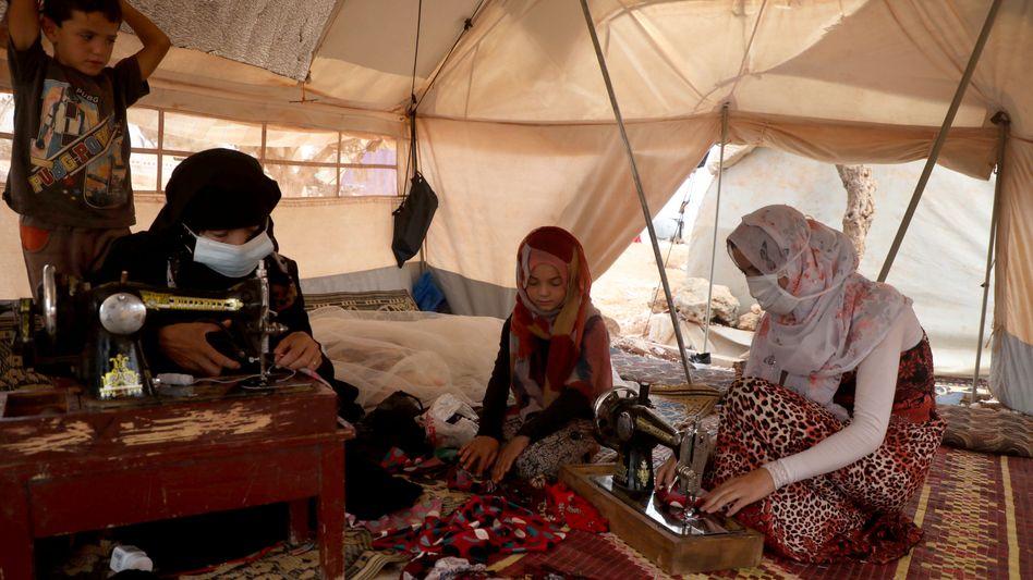 Vertriebene Syrerinnen nähen Corona-Schutzmasken in einem Camp in Maarat Misrin in der Region Idlib