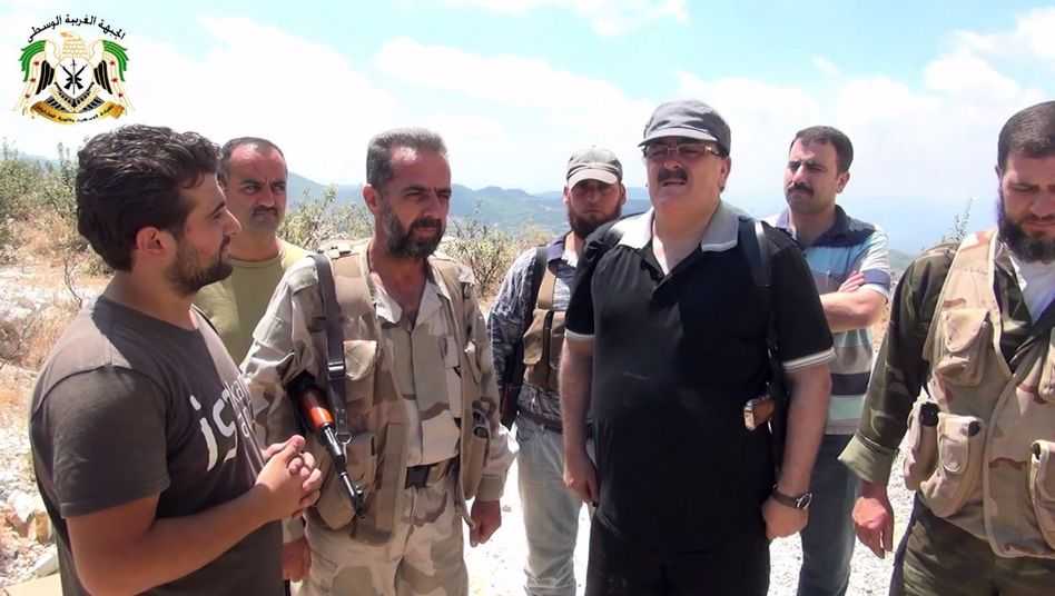 Syrian rebel leader Gen Salim Idris (in black shirt) speaks to rebel fighters on the outskirts of Latakia.